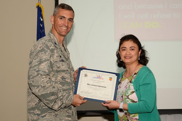U.S. Air Force Col. Daniel Lasica, 20th Fighter Wing commander, presents Maria Carina Tabalanza, 20th Component Maintenance Squadron executive assistant, with a certificate of appreciation at Shaw Air Force Base, S.C., April 13, 2017. Tabalanza was recognized for her efforts as a volunteer and 20th Fighter Wing Chapel Sunday school teacher. (U.S. Air Force photo by Airman 1st Class Kathryn R.C. Reaves)