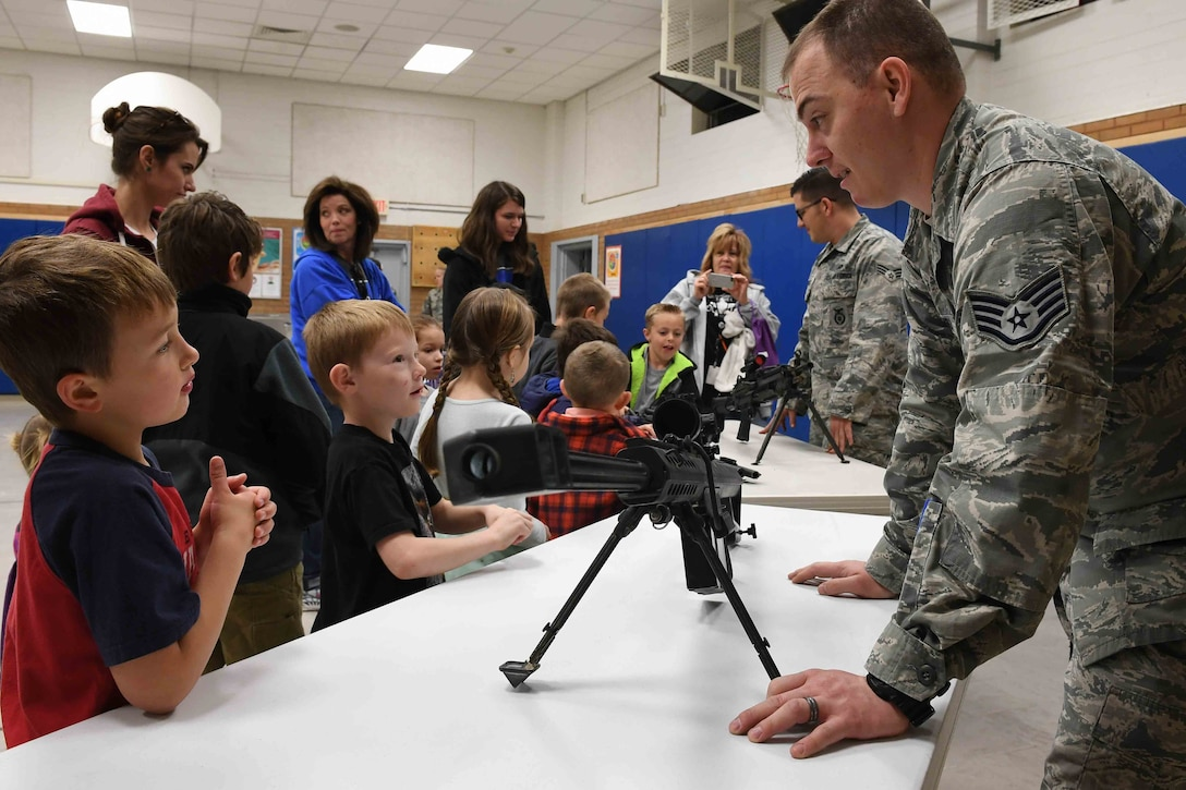 Staff Sgt. Ajay Rivera, 75th Security Forces Squadron combat arms instructor, shows children some military weapons during the Kids Deployment Day event, Hill Field Elementary School, Utah, April 4, 2017. (U.S. Air Force photo/R. Nial Bradshaw)