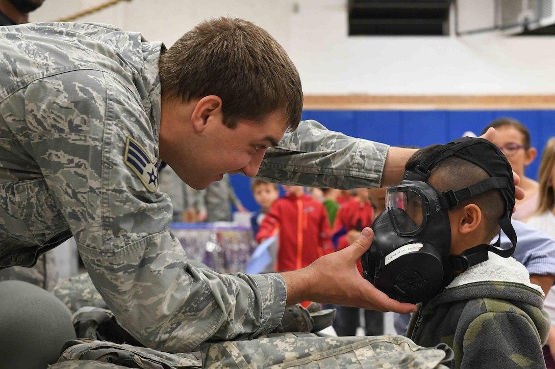 Senior Airman Jacob Peters, 75th Logistics Readiness Squadron, assists a student trying on a gas mask during the Kids Deployment Day event, Hill Field Elementary, Utah, April 14, 2017. (U.S. Air Force photo/R. Nial Bradshaw)