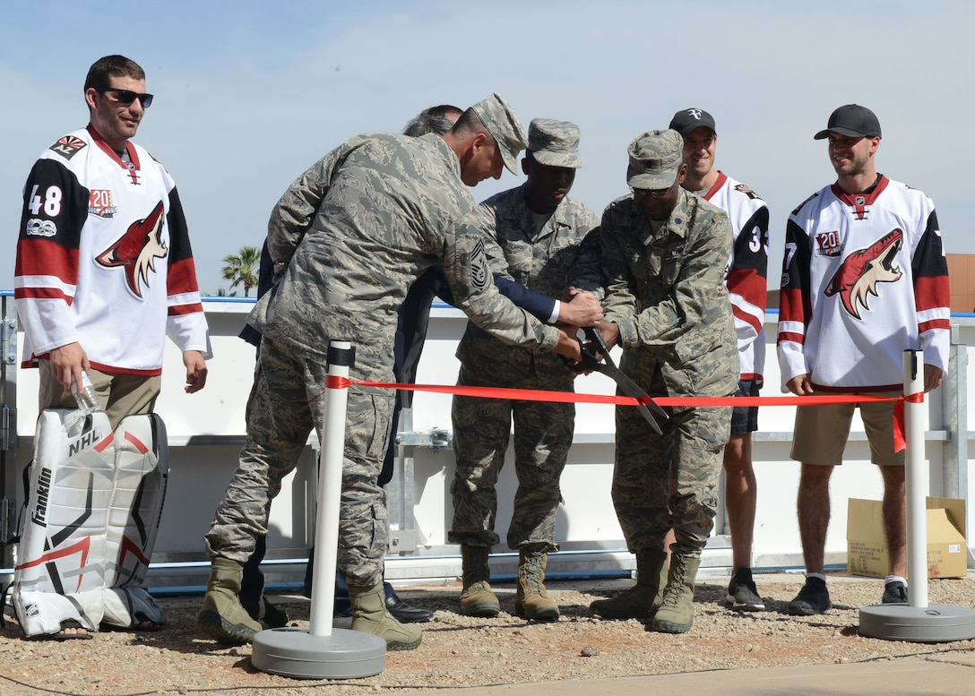 Lt. Col. Kevin Marzette, 56th Mission Support Group deputy commander, and Chief Master Sgt. Randall Kwiatkowski, 56th Fighter Wing command chief, cut the ribbon signifying the opening of the deck hockey rink April 13, 2017, at Luke Air Force Base, Ariz. The Arizona Coyotes attended the ceremony and held a skills clinic for Airmen afterwards. (U.S. Air Force photo by Senior Airman James Hensley)