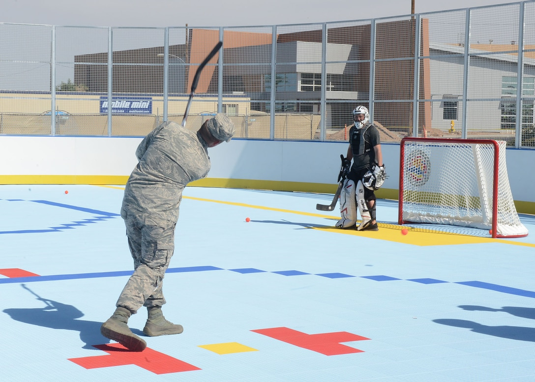 A Thunderbolt takes a shot against an Arizona Coyotes player after the ribbon cutting ceremony for the new hockey rink April 13, 2017, at Luke Air Force Base, Ariz. The rink is located adjacent to the base pool and Community Commons. (U.S. Air Force photo by Senior Airman James Hensley)