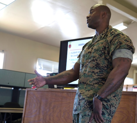 Maj. Jason Schneider, Commanding Officer for H&S Co., H&S Bn., MCI West - MCB Camp Pendleton, paces through an aisle whilst giving a brief on the Marine Corps Policy on social media April 13, 2017. Briefs like these are conducted to ensure that Marines stay up to date on all of the current Marine Corps Policies and regulations. (U. S. Marine Corps Photo by LCpl. Dylan Chagnon) levels adjusted and image cropped to highlight the subject.