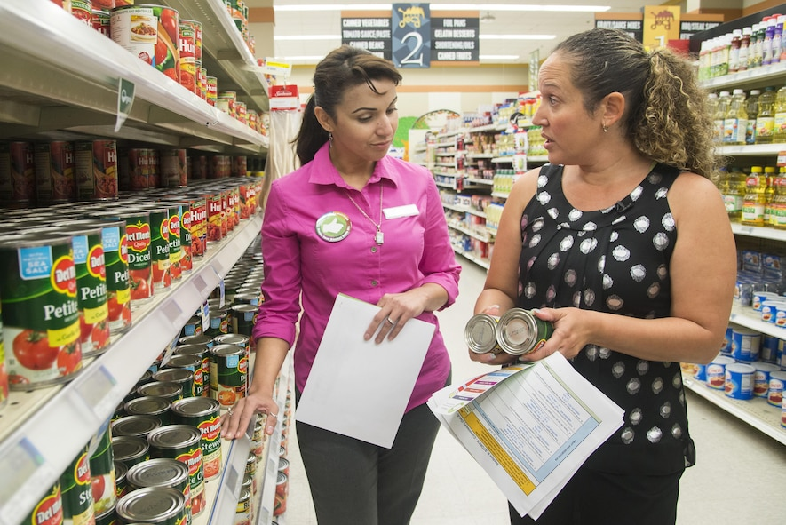 Claudia Smith (left), Commissary store manager, and Aracelis Gonzalez-Anderson, Health Promotions Program coordinator, discuss the contents of a can of tomatoes April 11, 2017, at Joint Base San Antonio-Randolph Commissary. The Health Promotions Services offer resources on eating healthy and promote living a fit lifestyle to JBSA personnel.