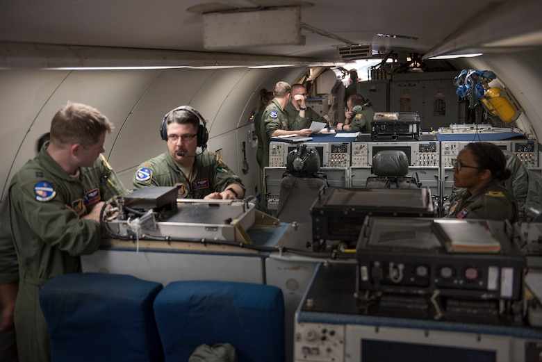 U.S. Air Force Airman 1st Class Favian Arteaga, 961st Airborne Air Control Squadron airborne surveillance technician (left), uses a communication system March 28, 2017, while flying in an E-3 Sentry over the Pacific Ocean. Airborne surveillance technicians make the initial identification of friend or foe aircraft and monitor their position. (U.S. Air Force photo by Senior Airman John Linzmeier/released)