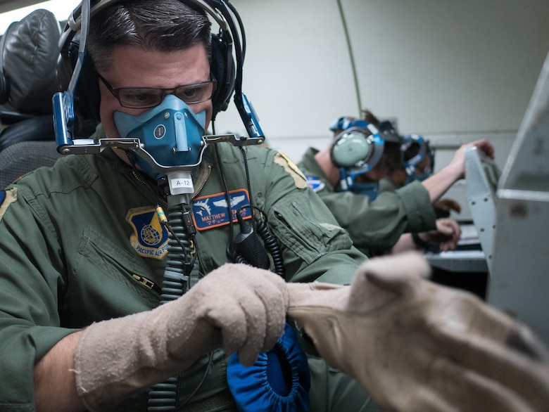 U.S. Air Force Maj. Matthew Starck, 961st Airborne Air Control Squadron mission crew commander, dawns individual protective gear for a rapid depressurization drill March 28, 2017, while flying in an E-3 Sentry over the Pacific Ocean. Aircrew members are constantly being tested on how to react in emergency scenarios during training operations. (U.S. Air Force photo by Senior Airman John Linzmeier/released)