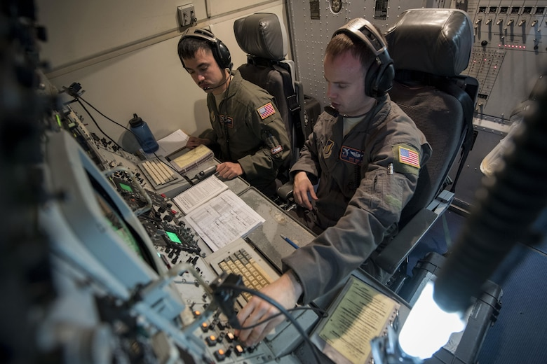 U.S. Air Force Staff Sgt. Anthony Lambrechts, 961st Airborne Air Control Squadron communication technician (left) and SSgt. Michael Burch, 961st AACS communication system operator, conduct a communications sweep March 28, 2017, during a training mission over the Pacific Ocean. Communications Airmen provide radio support to the aircrew, allowing for a secure means to communicate with partnered aircraft and various ground agencies. (U.S. Air Force photo by Senior Airman John Linzmeier/released)