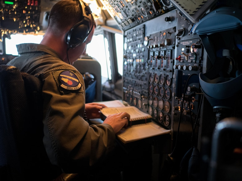 A U.S. Air Force flight engineer from the 961st Airborne Air Control Squadron monitors E-3 Sentry aircraft systems March 28, 2017, while flying in an over the Pacific Ocean. The flight engineer is the only enlisted Airman who operates in the Sentry's cockpit and acts as a bridge between the flight deck and mission crew. (U.S. Air Force photo by Senior Airman John Linzmeier/released)