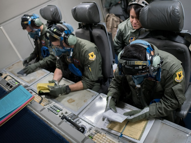 U.S. Air Force 961st Airborne Air Control Squadron airborne surveillance technicians conduct a crew coordination drill March 28, 2017, while flying in an E-3 Sentry over the Pacific Ocean. The team was evaluated as they went over emergency procedures and continued their job in a simulated depressurized atmosphere. (U.S. Air Force photo by Senior Airman John Linzmeier/released)