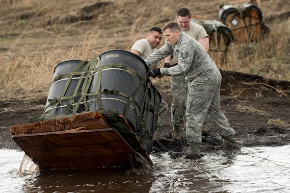 (Right to left) Staff Sgt. William McAtee, Tech Sgt. Daniel Blair, and Airman 1st Class Dominic Pacheco, all with the 374th Logistics Readiness Squadron combat mobility flight recovery team, pull a containerized delivery system bundle from a water at Combined Armed Training Center Camp Fuji, Japan, April 12, 2017. Airmen with the 374th Logistics Readiness Squadron and Eagle airlifts with the 36th Airlift Squadron conducted mass CDS airdrop training. (U.S. Air Force photo by Yasuo Osakabe)