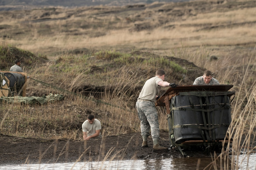 Airmen with the 374th Logistics Readiness Squadron combat mobility flight, recover a Containerized Delivery System bundle from a water at Combined Armed Training Center Camp Fuji, Japan, April 12, 2017. Airmen with the 374th Logistics Readiness Squadron and Eagle airlifts with the 36th Airlift Squadron conducted mass CDS airdrop training. (U.S. Air Force photo by Yasuo Osakabe)