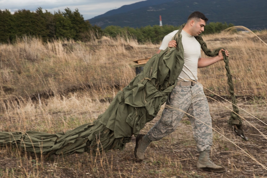 Airman 1st Class Dominic Pacheco, 374th Logistics Readiness Squadron combat mobility flight recovery team, carries an equipment parachute at Combined Armed Training Center Camp Fuji, Japan, April 12, 2017. Airmen with the 374th Logistics Readiness Squadron and Eagle airlifts with the 36th Airlift Squadron conducted mass CDS airdrop training. (U.S. Air Force photo by Yasuo Osakabe)
