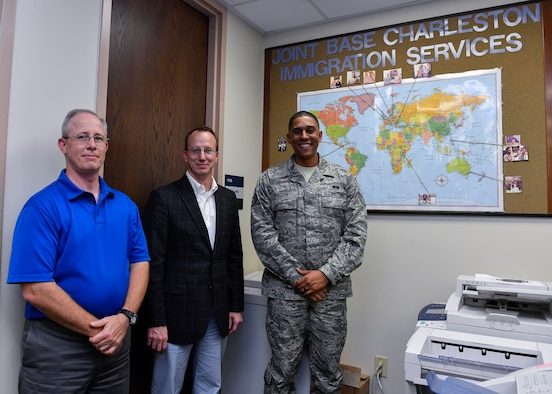 Robert Yancey, left, 628th Air Base Wing Office of the Staff Judge Advocate discharge clerk, Brad Stanley, center, 628th ABW JA Civil Law division chief, and Staff Sgt. William Haston, right, 628th ABW JA NCO in charge of military justice, showcase photos of a few of the people they have helped obtain citizenship here, April 13, 2017. Members of 628th ABW JA have assisted more than 300 service members and their families receive their citizenship since the Joint Base Charleston Immigration Clinic was created in 2008.