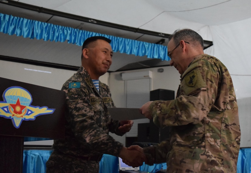Lt. Col. Bulat Dusembayev, commander of the Kazakhstan Peacekeeping Brigade, left, presents Lt. Col. James Becker, 352nd Civil Affairs Command, with a certificate of appreciation during the closing day of Steppe Eagle Koktem, Apr. 11, 2017, at Illisky Training Center, Kazakhstan.
