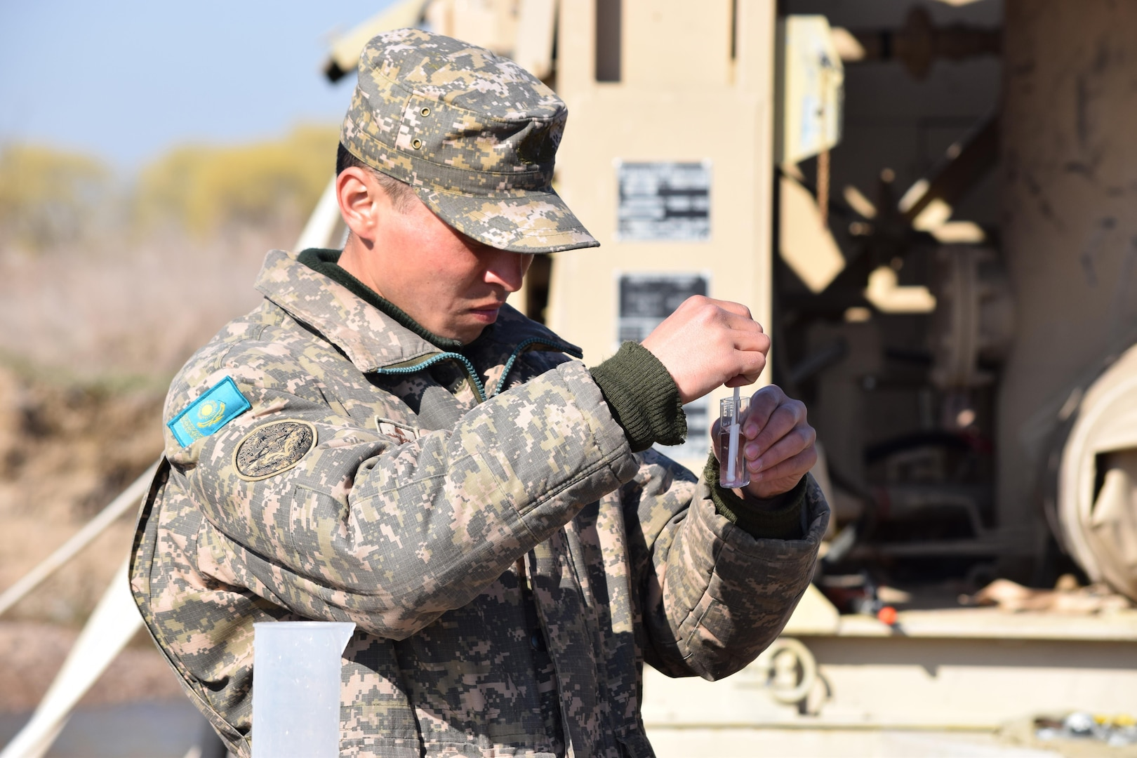 A soldier with the Kazakhstan Peacekeeping Battalion tests the level of chlorine in a beaker of purified water during a peacekeeping operations scenario for Steppe Eagle Koktem Apr. 9, 2017, at Illisky Training Center, Kazakhstan.