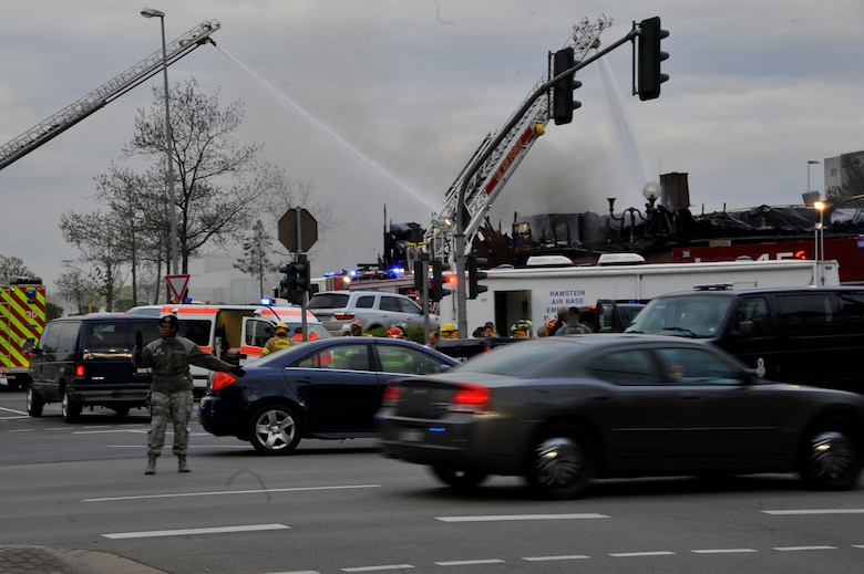 Airmen direct traffic at the scene of a fire at bldg. 1135, April 16, 2017 on Ramstein Air Base, Germany. According to base officials, the fire was contained and there was one minor injury, of a firefighter. The cause of the incident is under investigation. (U.S. Air Force photo by Airmen 1st Class D. Blake Browning)