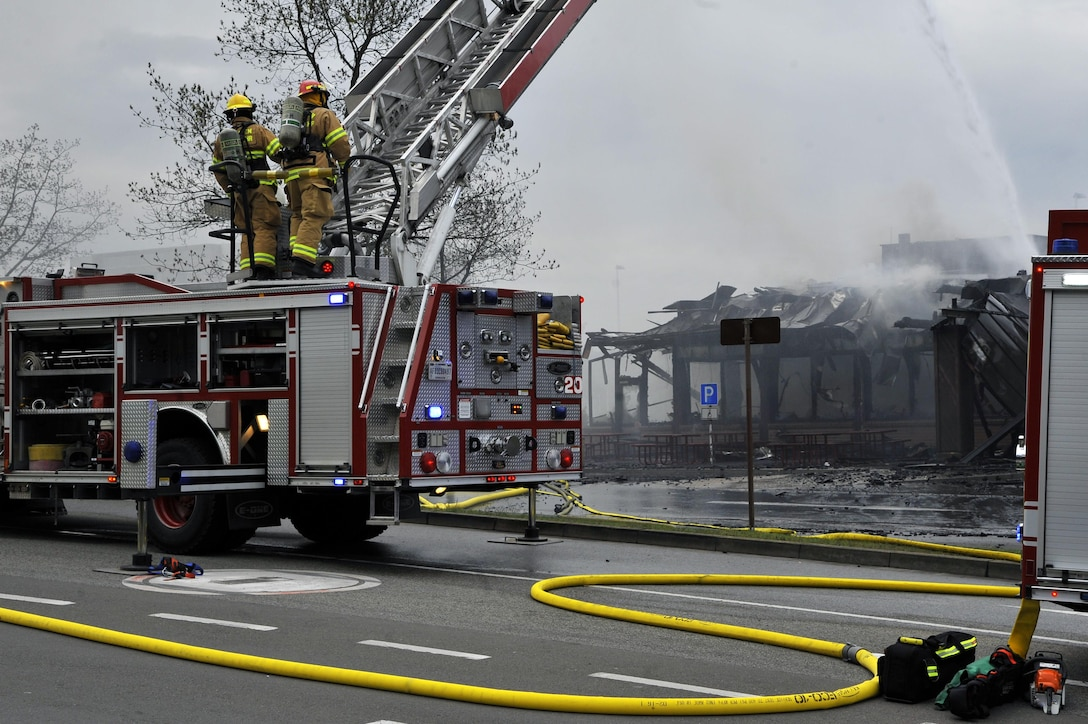 86th Civil Engineer Group Airmen operate an extendable ladder outside of a fire at bldg. 1135, April 16, 2017 on Ramstein Air Base, Germany. According to base officials, the fire was contained and there was one minor injury, of a firefighter. The cause of the incident is under investigation. (U.S. Air Force photo by Airmen 1st Class D. Blake Browning)