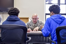 Lt. Col. John Kochansky, director of inspections with the 910th Inspector General office, helps Inspiring Minds students with schoolwork during a study and tutoring session April 13, 2017. Youngstown Air Reserve Station partners with Inspiring Minds, a non-profit K-12 youth organization based in Warren, Ohio, to provide mentorship and represent the Air Force Reserve as a career option. Volunteers from YARS devote personal time to mentorship, tutoring and fun activities with the students several times throughout the school year. (U.S. Air Force photo/Eric White)