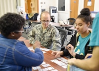 Senior Airman Nicholas Bacisin, a customer support technician here, plays a math-based card game and interacts with Inspiring Minds students during a study table, tutoring and fun session April 13, 2017. Youngstown Air Reserve Station partners with Inspiring Minds, a non-profit K-12 youth organization based in Warren, Ohio, to provide mentorship and represent the Air Force Reserve as a career option. Volunteers from YARS devote personal time to mentorship, tutoring and fun activities with the students several times throughout the school year. (U.S. Air Force photo/Eric White)