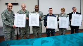 Base leadership pose for a photograph at Joint Base Andrews, Md., April 6, 2017. Leadership gathered to sign a Sexual Assault Awareness and Prevention Month 2017 proclamation that kicked off the month's various events. (U.S. Navy photo by Petty Officer 1st Class Ernesto Hernandez Fonte)