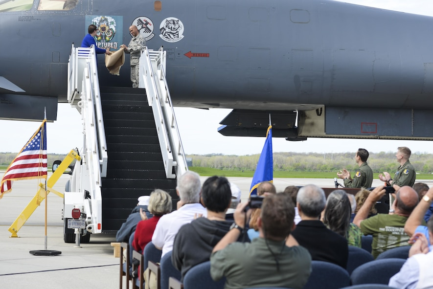 Becky Thatcher, daughter of the late Doolittle Raider Staff Sgt. David Thatcher, and U.S. Air Force Tech. Sgt. William Hatten, 28th Maintenance Squadron from Ellsworth Air Force Base, S.D., Ruptured Duck dedicated crew chief, unveil the newest rendition of the Ruptured Duck artwork in front of a crowd during a ceremony, Apr. 17, 2017 at Wright-Patterson Air Force Base, Ohio. The original artwork featured cross-eyed duck, wearing a leather helmet, staring out over crossed crutches. (U.S. Air Force photo by Wesley Farnsworth)