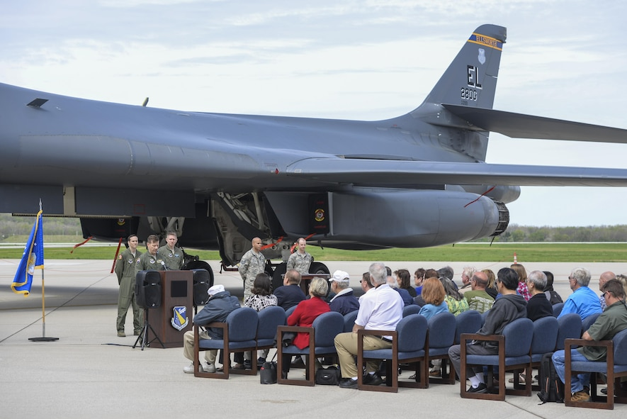 """U.S. Air Force Col. John Martin, 28th Operations Group commander from Ellsworth Air Force Base, S.D., addresses a crowd consisting of retired Doolittle Raider, Lt. Col. Dick Cole, along with family and friends of deceased Doolittle Raiders, during an unveiling ceremony for the new Ruptured Duck artwork, Apr. 17, 2017 at Wright-Patterson Air Force Base, Ohio.  The Ruptured Duck history began when pilot Ted Lawson scraped the tail of his B-25 when he pointed the nose of the aircraft too high before takeoff. His aircraft was then chalked with the """"Ruptured Duck"""", and later the first caricature of the angry duck with crutches was painted on the nose. (U.S. Air Force photo by Wesley Farnsworth)"""