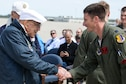 Retired Doolittle Raider, Lt. Col. Dick Cole, presents U.S. Air Force Capt. Michael Riddick, 34th Bomb Squadron B-1 pilot, with a coin at the conclusion of an unveiling ceremony for the new Ruptured Duck artwork, Apr. 17, 2017 at Wright-Patterson Air Force Base, Ohio.  The 34th Bomb Squadron lineage can be traced to one of the original Doolittle Raider squadrons. (U.S. Air Force photo by Wesley Farnsworth)