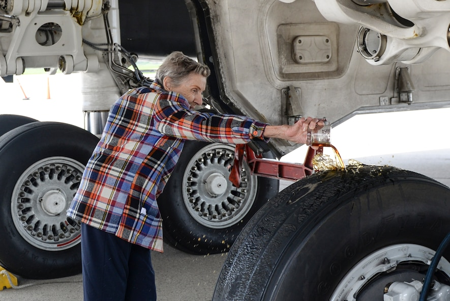 Dawn Thatcher, wife of the late Doolittle Raider Staff Sgt. David Thatcher, pours three fingers of Hennessey on the landing gears of the Ruptured Duck B-1 Aircraft, as part of a ceremony for the new Ruptured Duck artwork, Apr. 17, 2017 at Wright-Patterson Air Force Base, Ohio. The pouring of the most elite of fluids is a long held superstition, which is said to provide a safe flight for those that serve on the aircraft. (U.S. Air Force photo by Wesley Farnsworth)