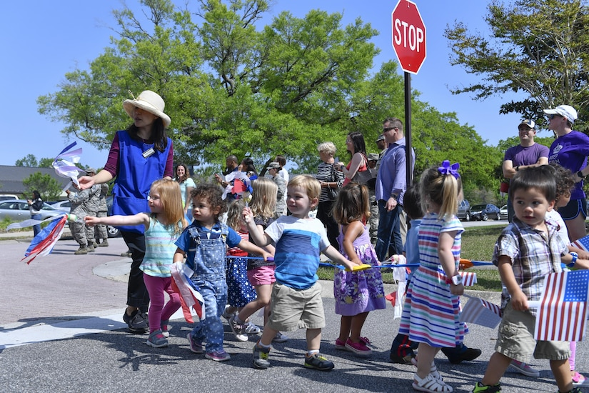 Members of Team Charleston from the Childcare Development Center hold up signs during a parade here for a Month of the Military Child celebration, April 14, 2017. April is designated as Month of the Military Child to recognize the 1.7 million military children across the globe and the sacrifices they make alongside their parents.