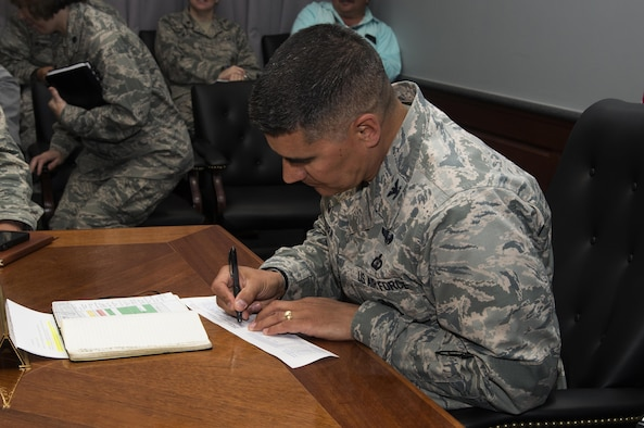 Col. Eric Shafa, 42nd Air Base Wing Commander, fills out an AF 2561 Contribution Form, during the weekly wing staff meeting, April 17, 2017, Maxwell Air Force Base, Ala. Following the meeting, refreshments were offered along with more information about the campaign.To donate, visit  www.afassistancefund.org. (U.S. Air Force photo/ Senior Airman Alexa Culbert)