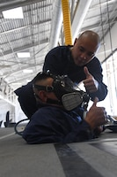 """U.S. Air National Guard members Senior Airman Allan Tan assists Senior Airman Pedro Pescador with the 146th Airlift Wing's Aircraft Fuel Systems Maintenance Squadron as he inserts himself into inside of a wing of a C-130J aircraft for a """"confined space rescue exercise"""" at the Channel Islands Air National Guard Station Port Hueneme, Calif. April 1, 2017. During a confined space rescue exercise, first-responders with the 146th Airlift Wing's Aircraft Fuel Systems Maintenance Squadron and Federal Fire Ventura County firefighters run through the critical emergency operations that would take place if a fuel-cell maintenance worker were to become incapacitated while working inside the very small fuel tanks inside the aircraft's wings. (U.S. Air National Guard photo by: Staff Sgt. Nieko Carzis.)"""