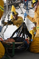 "Federal Fire Ventura County Firefighter Michael Barnett and Firefighter David Yi prepare a transport litter stretcher to lower Senior Airman Pedro Pescador with the 146th Airlift Wing's Aircraft Fuel Systems Maintenance Squadron off the wing of a C-130J aircraft during a ""confined space rescue exercise"" at the Channel Islands Air National Guard Station Port Hueneme, Calif. April 1, 2017. During a confined space rescue exercise, first-responders with the 146th Airlift Wing's Aircraft Fuel Systems Maintenance Squadron and Federal Fire Ventura County firefighters run through the critical emergency operations that would take place if a fuel-cell maintenance worker were to become incapacitated while working inside the very small fuel tanks inside the aircraft's wings. (U.S. Air National Guard photo by: Staff Sgt. Nieko Carzis.)"