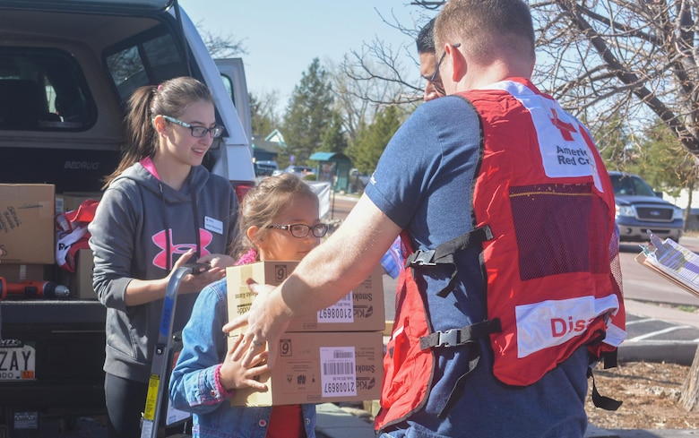SCHREIVER AIR FORCE BASE, Colo. -- Katie Chandler hands her father, Capt. Allen Chandler, 6th Space Operations Squadron, a box of fire alarms that 310th Space Wing volunteers will install for local families during a Home Fire Campaign event on Saturday, Apr. 15th, 2017. The Red Cross responds to approximately 64,000 disasters each year with the vast majority being home fires, resulting in a goal to reduce fire-related deaths and injuries. (U.S. Air Force photo/Senior Airman Laura Turner)