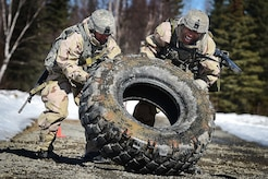 "Army Pfc. Esteban Guerrero, a native of Modesto, Calif., left, and Spc. Diego Adamski, a native of Shelton, Wash., both assigned to the 95th Chemical Company, ""Arctic Dragons"", 17th Combat Sustainment Support Battalion, U.S. Army Alaska, flip a tire to elevate their heart rates before executing a Joint Service Lightweight Integrated Suit Technology stress fire at McGee range on Joint Base Elmendorf-Richardson, Alaska, April 13, 2017. The JSLIST is the product of a four-Service effort to field a common chemical protective clothing ensemble including a lightweight protective garment, multi-purpose overboots and gloves."