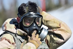 "Army Pfc. Esteban Guerrero, a native of Modesto, Calif., assigned to the 95th Chemical Company, ""Arctic Dragons"", 17th Combat Sustainment Support Battalion, U.S. Army Alaska, donns his protective mask before executing a Joint Service Lightweight Integrated Suit Technology stress fire at McGee range on Joint Base Elmendorf-Richardson, Alaska, April 13, 2017. The JSLIST is the product of a four-Service effort to field a common chemical protective clothing ensemble including a lightweight protective garment, multi-purpose overboots and gloves."
