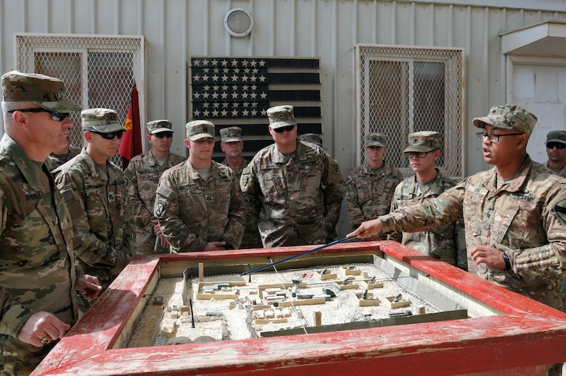 Spc. Billy Kong, radio telephone operator for Charlie Company, 1st Battalion, 12th Cavalry Regiment, briefs Brig. Gen. John Epperly, Deputy Commanding General for the 29th Infantry Division, on the layout and function of his battery's Patriot site March 26, 2017 in Bahrain. Kong was awarded a coin from Epperly for his presentation. Military coins are traditionally given by senior leaders in recognition for performance and excellence.  (U.S. Army photo by Sgt. Kelly Gary, 29th Infantry Division Public Affairs)