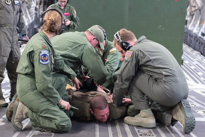 Master Sgt. Joshua Manhart, a volunteer simulated patient, simulates having a mental breakdown and being restrained by aeromedical technicians from the 146th Aeromedical Evacuation Squadron, California Air National Guard, while training on a C-17 Globemaster III during the Multiple Aircraft Training Opportunity Program (MATOP) organized by the 137th Aeromedical Evacuation Squadron from Will Rogers Air National Guard Base, Oklahoma City, April 7, 2017. Airmen of the 137 AES were joined by eight of the nine Air National Guard aeromedical evacuation squadrons as they hosted the annual training event and accomplished mandatory annual aeromedical training requirements. (U.S. Air National Guard photo by Senior Master Sgt. Andrew M. LaMoreaux/Released)