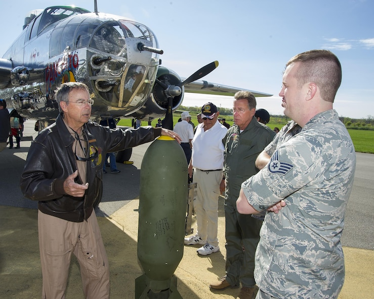 Larry Kelly talks with Staff Sgt. Andrew Wanros, 175th Wing Maryland Air National Guard, in front of Kelly's B-25 Mitchell Bomber on a runway by the National Museum of the U.S. Air Force at Wright-Patterson Air Force Base, Ohio, April 17, 2017. Wanros traveled to Wright-Patterson AFB to take part in the museum's celebration of the 75th anniversary of the Doolittle Raid when Army Air Corps bombers took off from an aircraft carrier to deliver the first strike of the war on the Japanese homeland. (U.S. Air Force photo by R.J. Oriez)