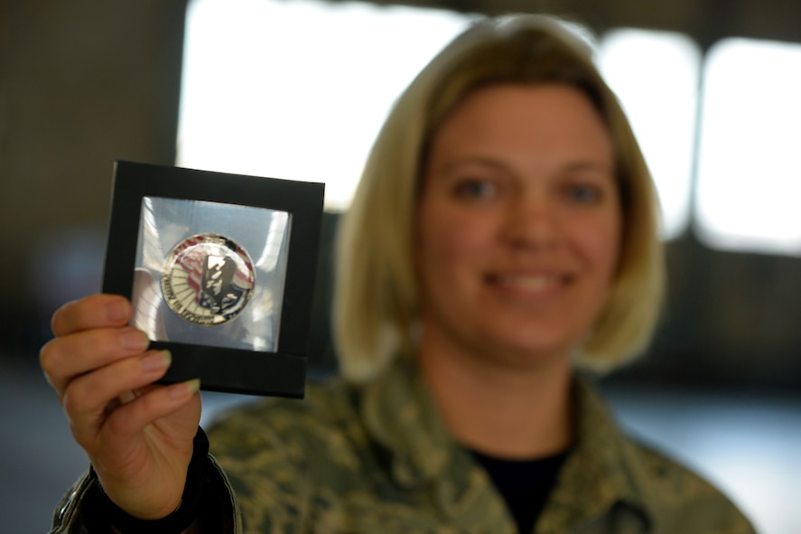U.S. Air Force Master Sgt. Kristin Bandy, with the 121st Medical Squadron, shows off her Airman-to-Airman coin during the 121st Air Refueling Wing awards ceremony April 2, 2017 at Rickenbacker Air National Guard Base, Ohio. Bandy received numbered coin 80 for her efforts in improving the Airmen's experience in the medical clinic. (U.S. Air National Guard photo by Senior Master Sgt. Ralph Branson)