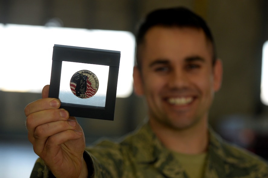 U.S. Air Force Tech. Sgt. Josh Sparks, with the 121st Maintenance Squadron, shows off his Airman-to-Airman coin during the 121st Air Refueling Wing awards ceremony April 2, 2017 at Rickenbacker Air National Guard Base, Ohio. Sparks received numbered coin 58 for aiding multiple squadrons across the Wing with the design and application of stencils and decals to enhance the work areas and create esprit de corps. (U.S. Air National Guard photo by Senior Master Sgt. Ralph Branson)