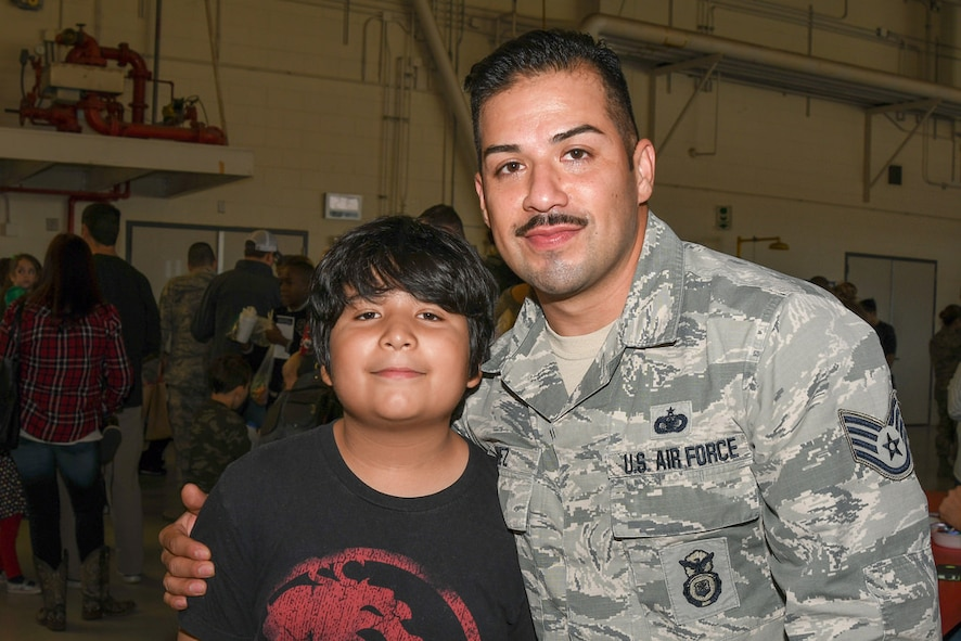 Staff Sgt. Juan Nunez a security forces specialist with the 136th Security Forces Squadron, Texas Air National Guard, and his son pose for a photo at the 136th Airlift Wing's Annual Children's Christmas party Nov. 20, 2016 at Naval Air Station Fort Worth Joint Reserve Base, Texas. (Air National Guard photo by Tech. Sgt. Vanessa Reed)