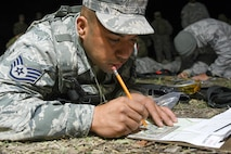 Air Force Staff Sgt. Juan Nunez, a security forces specialist with the 136th Security Forces Squadron, Texas Air National Guard, Fort Worth, Texas, plots points on his map during the land navigation event during the 2017 Texas Military Department Best Warrior Competition, March 2, 2017 at Camp Swift, near Bastrop, Texas. Land navigation tests the competitors ability to read maps, use a compass and other skills to traverse through unfamiliar terrain to different points throughout the course. (Air National Guard photo by Senior Airman De'Jon Williams)