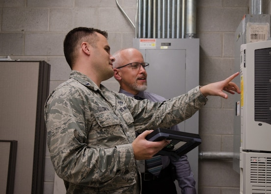 From left, Capt. Tanner Smith, AFCEC's Operations Maintenance Division branch chief, and Bryan Muller, operations management SME, analyze maintenance data on a mobile data device.  The operations directorate is testing the device and hoping to field it with CE operations flights in the near future. Tanner was recently selected as Air Force Installation and Mission Support Center and Air Force Materiel Command Company Grade Officer of the Year.