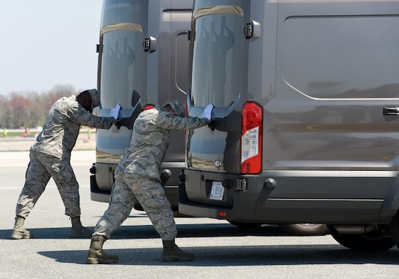 Airman 1st Class Emmanuel Yeboah and Senior Airman Cody Kendall, both assigned to the Air Force Mortuary Affairs Operations, simultaneously close the doors of the mortuary transfer vehicles during Folded Flag 2017 April 11, 2017, on Dover Air Force Base, Del. U.S. Army and Marine Corps carry teams and AFMAO personnel participated in the joint service training exercise that tested the ability of AFMAO to respond to a mass casualty incident. (U.S. Air Force photo by Roland Balik)