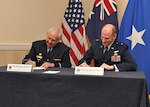 DLA Energy Commander Air Force Brig. Gen. Martin Chapin, right, and Air Commodore Stephen Winterton, Director General Fuels Services Branch, Joint Logistics Command at Department of Defense of Australia, sign the new Fuel Exchange Agreement between Australia and the U.S. April 12 during the DLA Energy Worldwide Energy Conference.