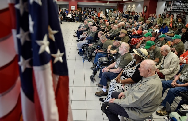 Korean War veterans who are residents of the State of Oklahoma Veterans Home, Norman, Oklahoma, are framed by the American flag as they listen to remarks given by Lt. Gen. Lee K. Levy II, Air Force Sustainment Center commander, as he recognizes their service March 30, 2017. Many of the veterans are wearing donated commemorative shirts honoring them. (U.S. Air Force photo/Greg L. Davis)