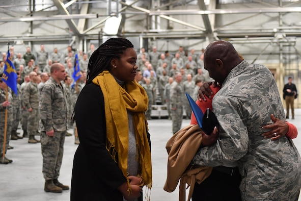 Col. Rodney Lewis, 319th Air Base Wing commander, embraces his wife as his daughter watches, after his final all call as the base commander on Grand Forks Air Force Base, N.D., April 14, 2017. Lewis and his family left Grand Forks AFB for the Pentagon as Lewis takes the position of director of the executive action group for the Air Force Chief of Staff. (U.S. Air Force photo by Airman 1st Class Elijaih Tiggs)