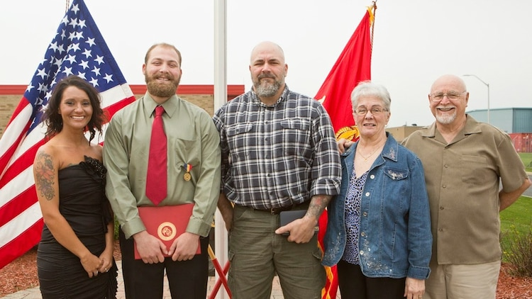 Cpl. Nathan Bryson poses for a photo with his girlfriend, father and grandparents after being awarded the Navy and Marine Corps Medal in Brook Park, Ohio, April 13, 2017. In 2014, Bryson and a fellow Marine helped rescue an elderly man from a burning vehicle. A Marine Corps veteran, Bryson most recently served as a motor transport operator for Headquarters and Support Battalion, School of Infantry East, Camp Lejeune, North Carolina. The Navy and Marine Corps Medal is awarded for acts of heroism despite personal risk and is the highest honor one can achieve for non-combat service. (U.S. Marine Corps Photo by Cpl. Dallas Johnson/Released)