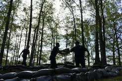 Volunteers from the Fort Eustis Fire Department place sandbags at a Civil War earthworks site on Fort Eustis during Earth Week events at Joint Base Langley-Eustis, Va., April 17, 2017.  Preserving this earthwork was part of JBLE's Earth Week celebration, which also included shoreline planting, boat tours, nature trail maintenance and a rain-barrel workshop. (U.S. Air Force photo/Tech. Sgt. Katie Gar Ward)