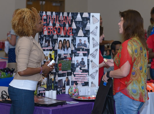Barbara Walker, 335th Training Squadron curriculum developer, provides information to Jemina Ballard, 81st Force Support Squadron human resource specialist, at the Women's History Month Information Fair and Panel event at the Roberts Consolidated Aircraft Maintenance Facility Auditorium, March 31, 2017, on Keesler Air Force Base, Miss. Walker discussed the benefits of the symposium and power of women networking around the base. (U.S. Air Force photo by Andre' Askew)