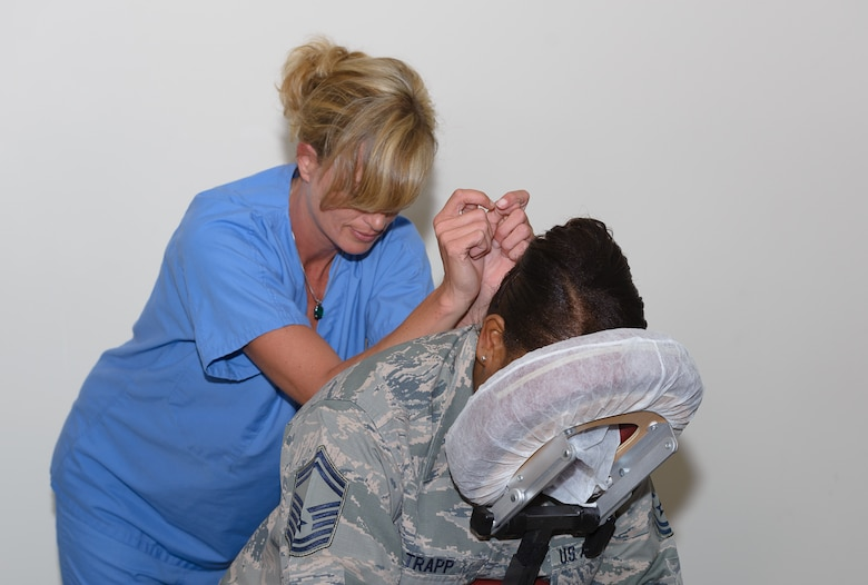 Senior Master Sgt. Lacreshia Trapp, 81st Communications Squadron superintendent, receives a massage from Chasity Nichols, Health and Wellness Center licensed massage therapist, at the Women's History Month Information Fair and Panel event at the Roberts Consolidated Aircraft Maintenance Facility Auditorium, March 31, 2017, on Keesler Air Force Base, Miss. Nichols performed a deep tissue massage to release chronic muscle tension in concentrated areas of the body. (U.S. Air Force photo by Andre' Askew)